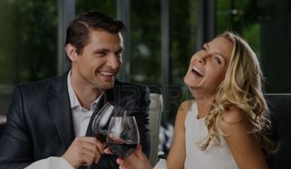 A happy couple enjoying a bottle of wine together.