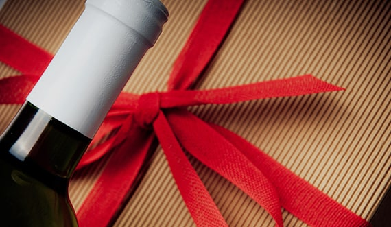 A bottle of wine and a brown box wrapped with a red ribbon